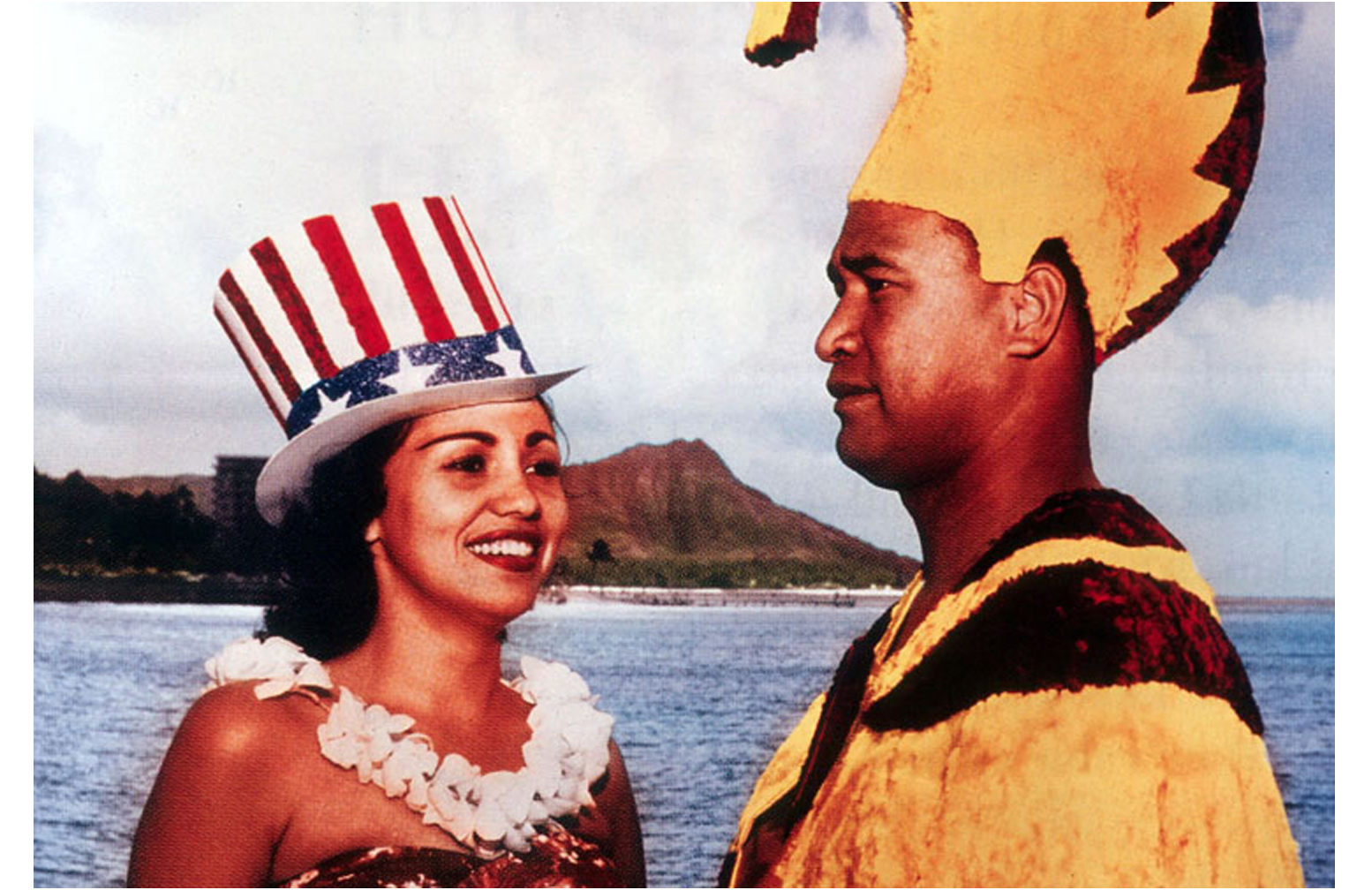 postcard picture of hawaiian lady in  a red, white & blue hat standing next to man in ahawaiian cloak & hat with Diamond Head in the background.